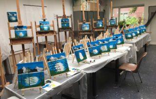 Een rij ezels en een rij tafels in het schilders atelier met Bob Ross schilderijen in wording