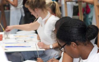 vriendinnen aan het werk achter ezels tijdens een vrijgezellenfeest met de Workshop naakt model tekenen en schilderen in Amsterdam