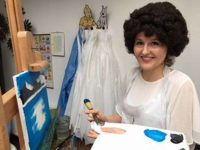 single lady with putty knife, palette and Bob Ross wig paints on a landscape