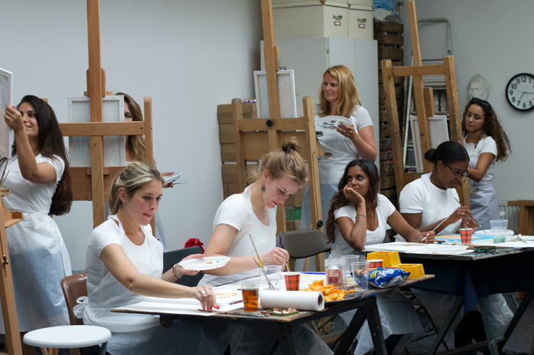 friends working behind easels and tables at a hen party for a life drawing session in an artist studio in Amsterdam